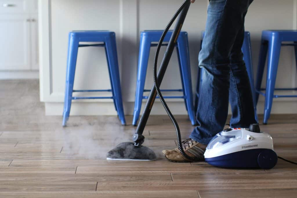 Person cleaning the floor tile grout with steam
