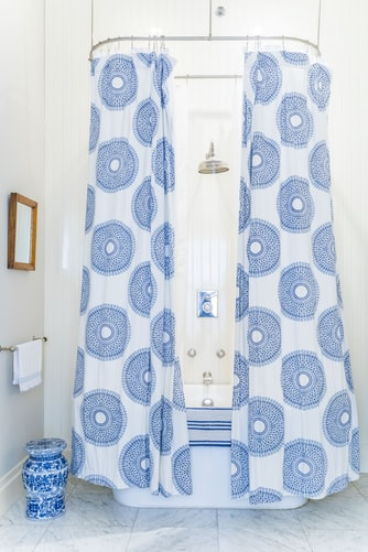 Printed white and blue curtain in a curved shower rod