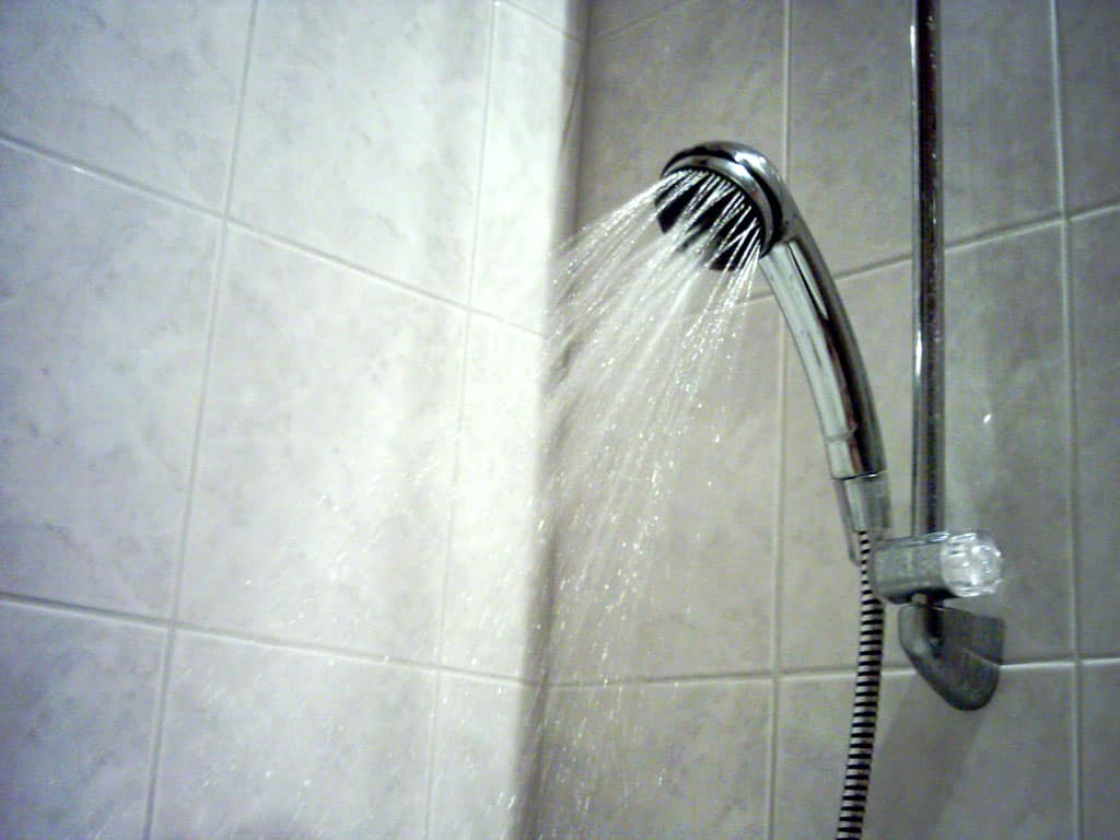 Water flowing out of a handheld shower head for low water pressure