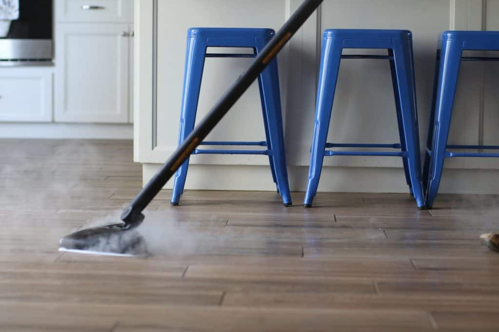 Steam mop cleaning a wooden floor