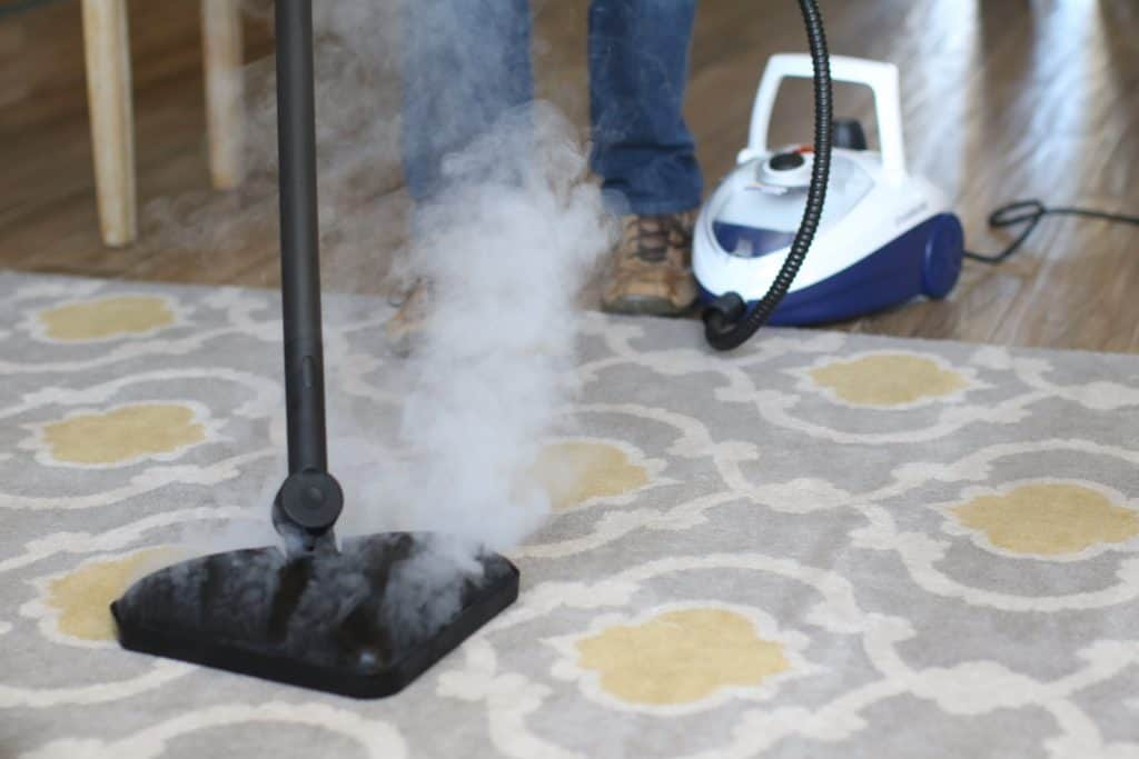 Person cleaning the carpet with steam cleaner