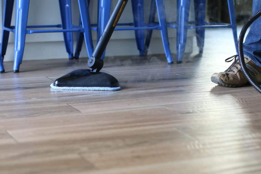 Person using a steam mop in a laminate flooring