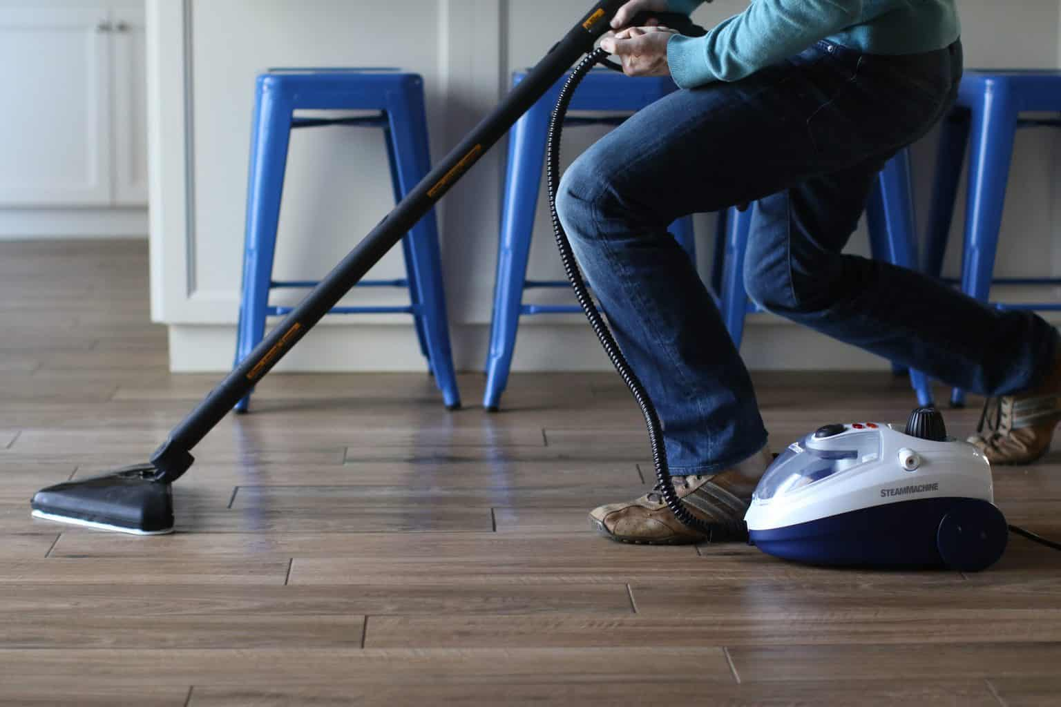 Person using a steam mop to clean a wood floor
