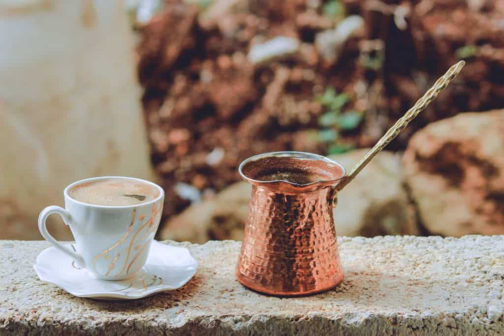Copper mug beside a cup of coffee