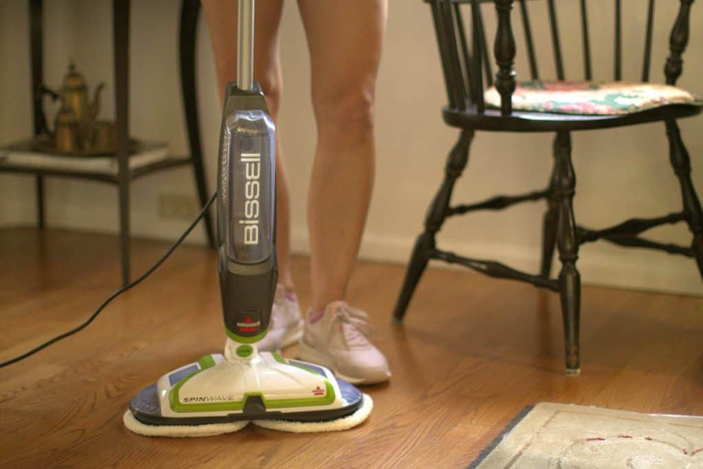 Person using a BISSELL Spinwave to mop her wooden floors