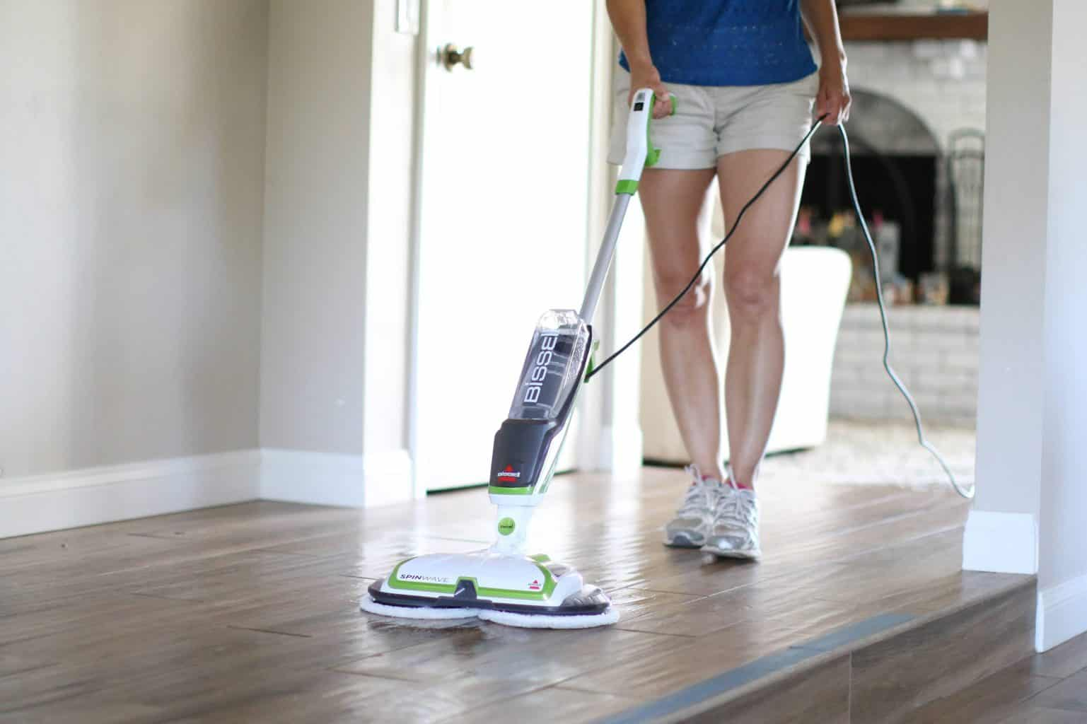 Woman using a mop while wondering what is dry mopping