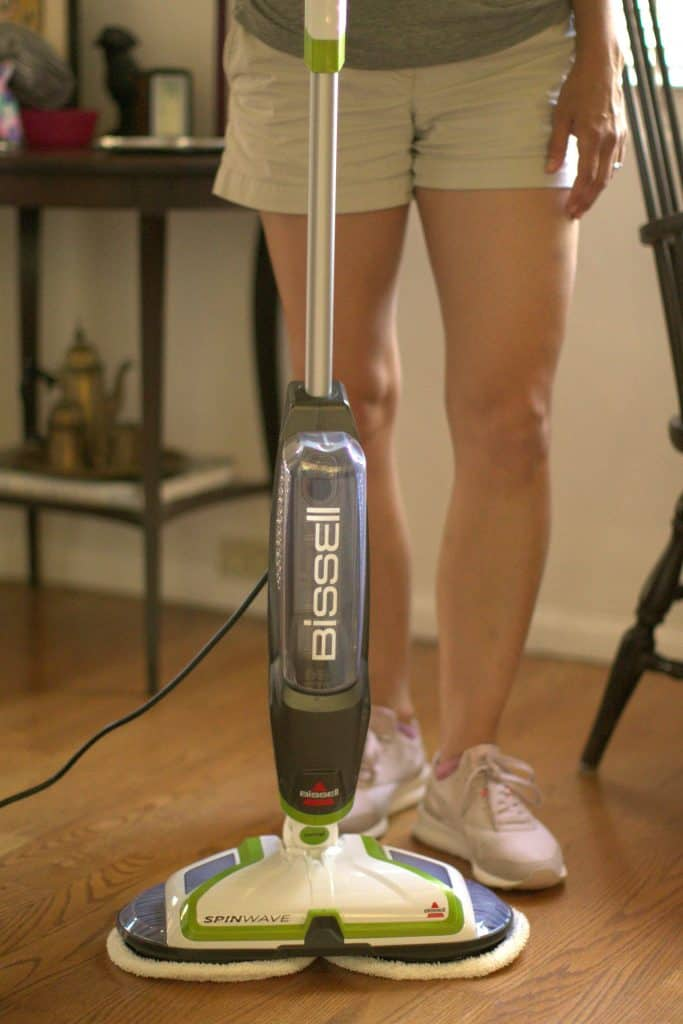 Woman using a BISSELL Spinwave Powered Hardwood Floor Mop and Cleaner