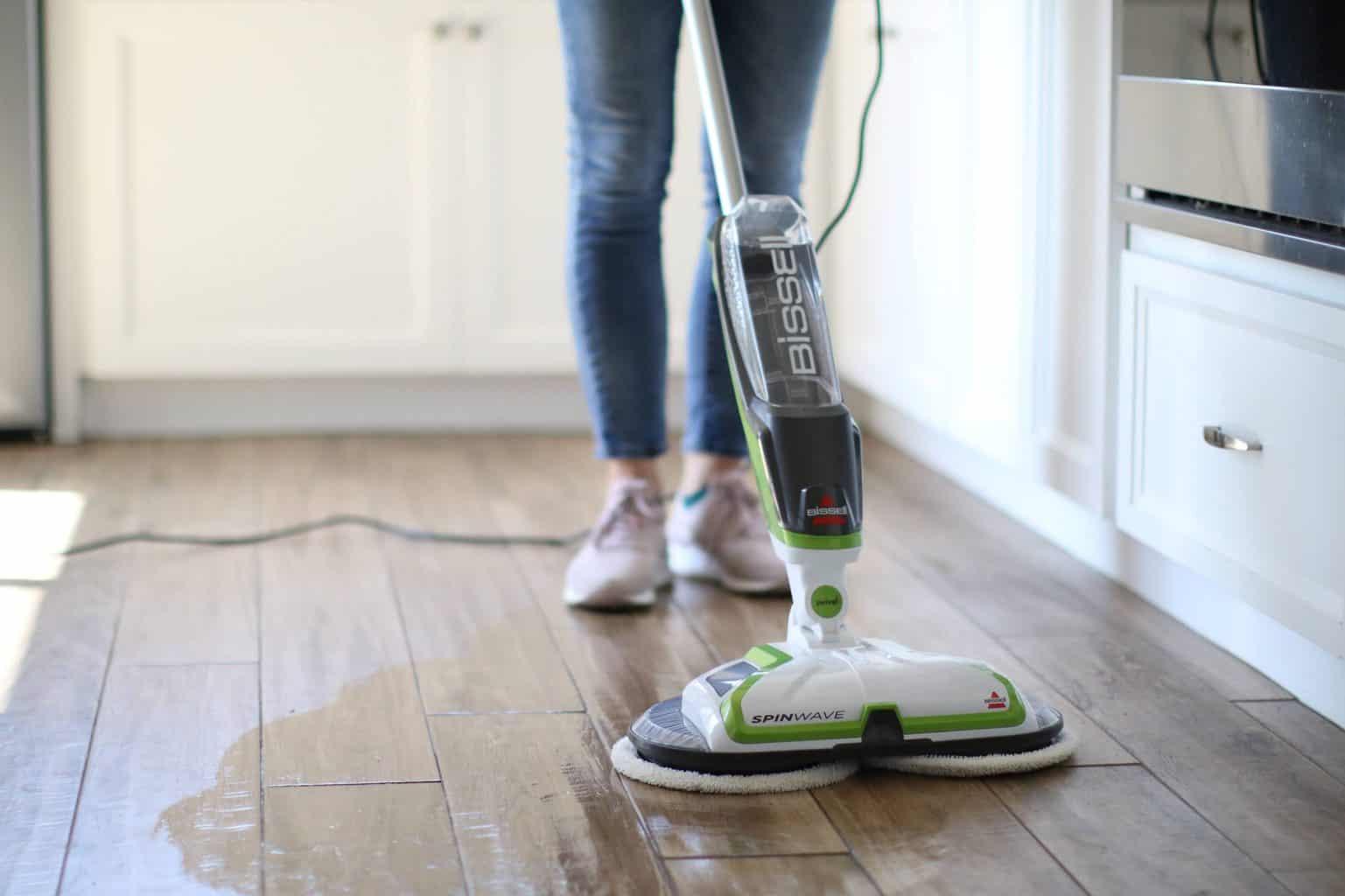 Woman using a wet mop on a wooden floor