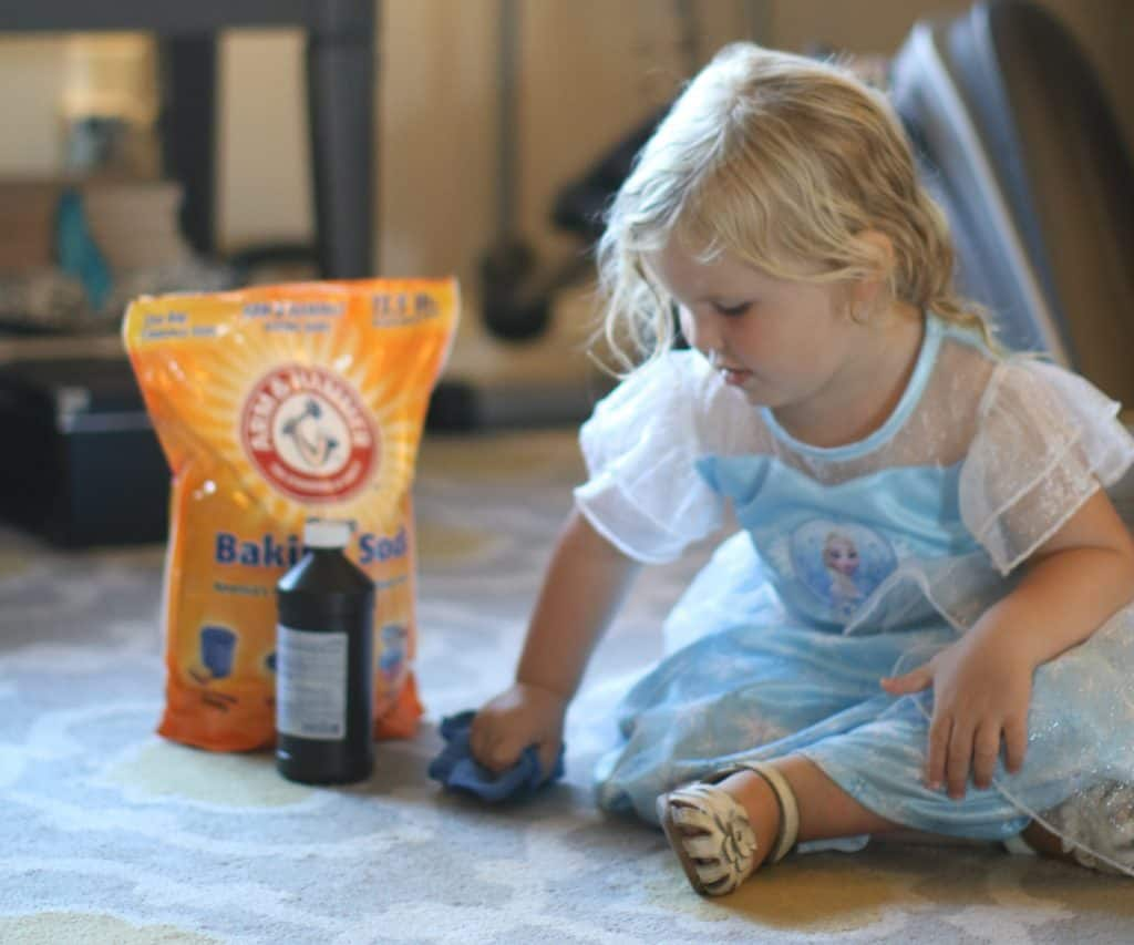 Child sitting beside a bottle and a pack of baking soda
