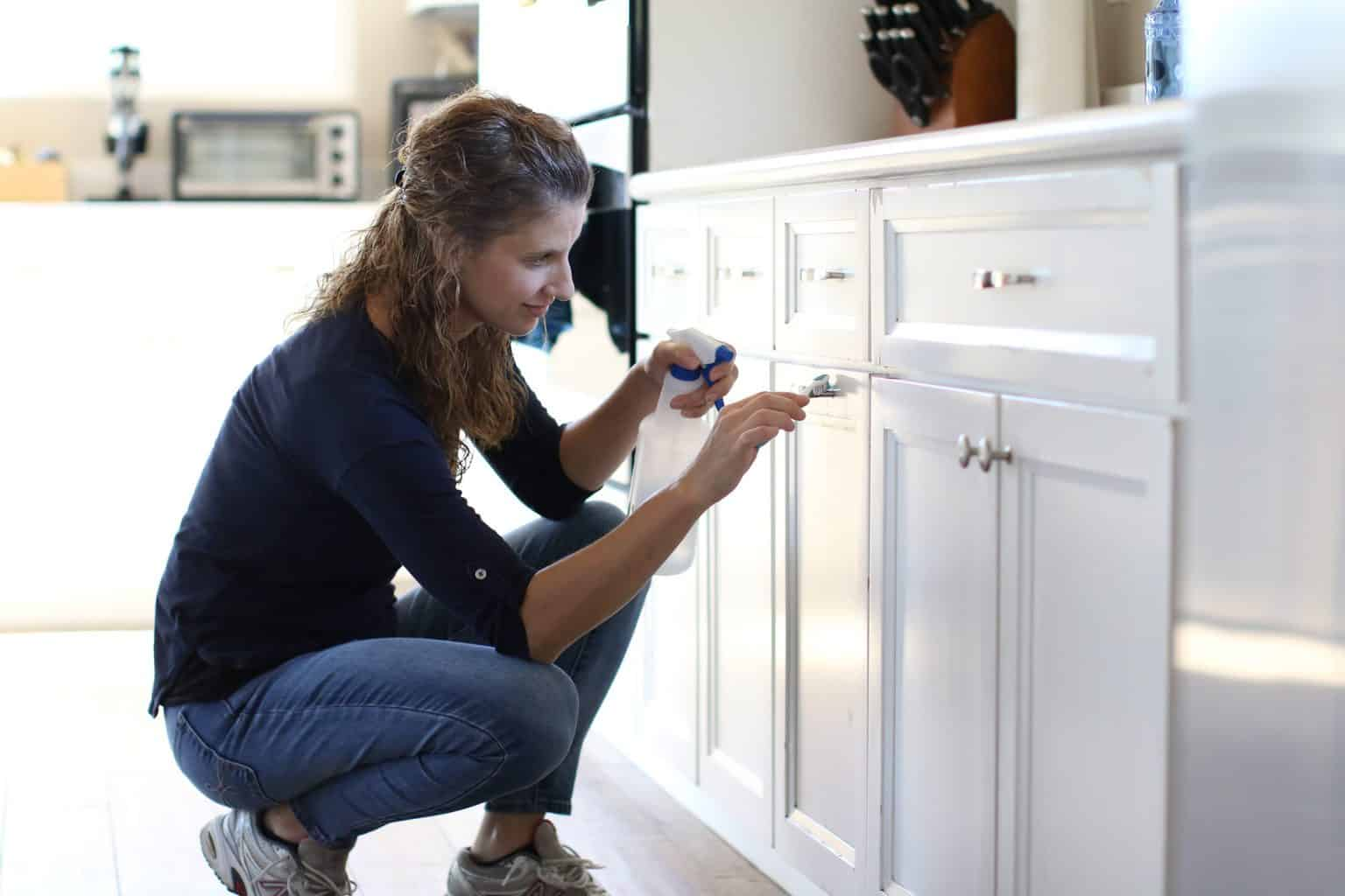 Woman spraying her kitchen cabinet with a cleaning solution