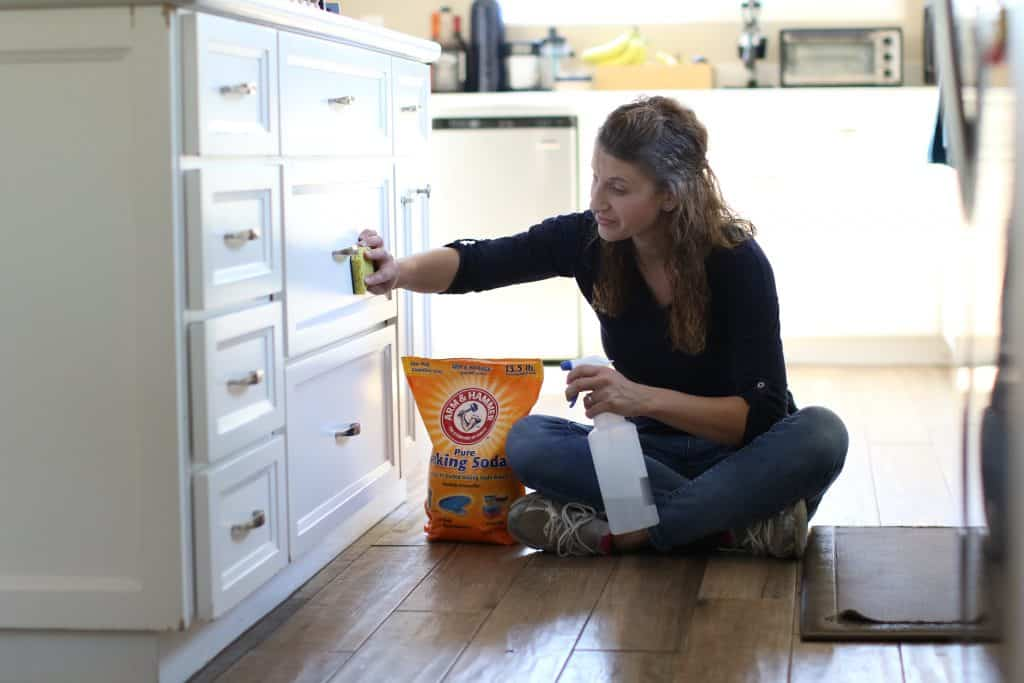 Woman sitting down on the floor while cleaning her kitchen cabinet