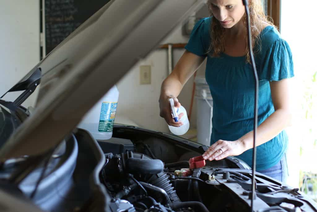 Woman spraying a DIY cleaning solution to her car battery terminal