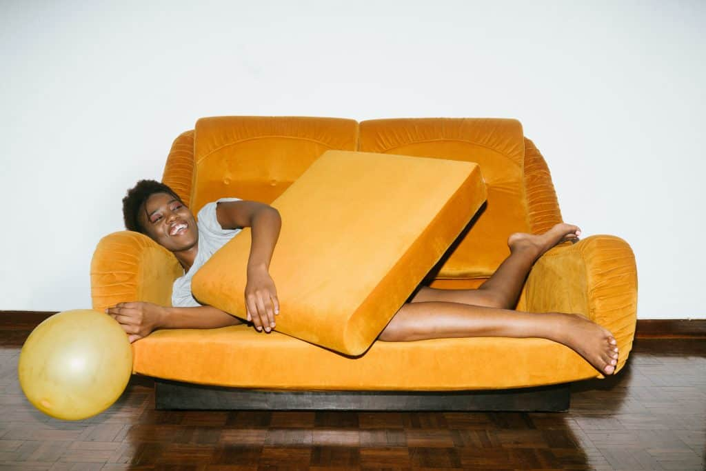 Woman lying on a suede couch