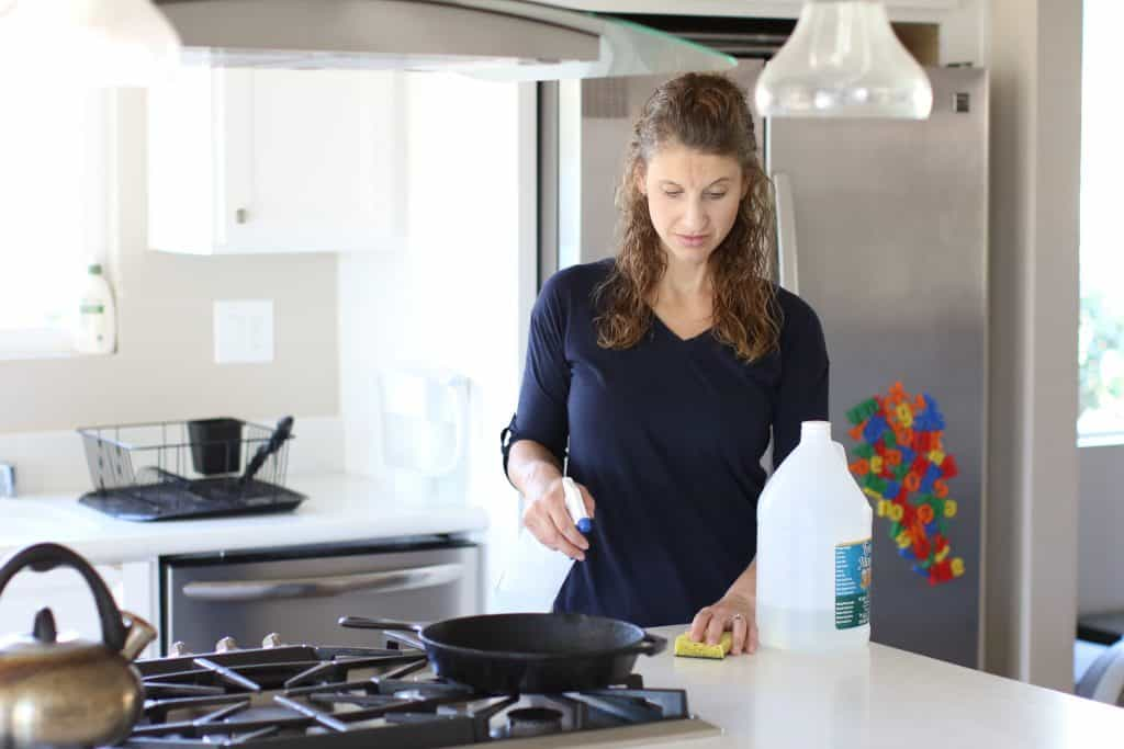 Woman spraying homemade cleaning solution to clean her countertop