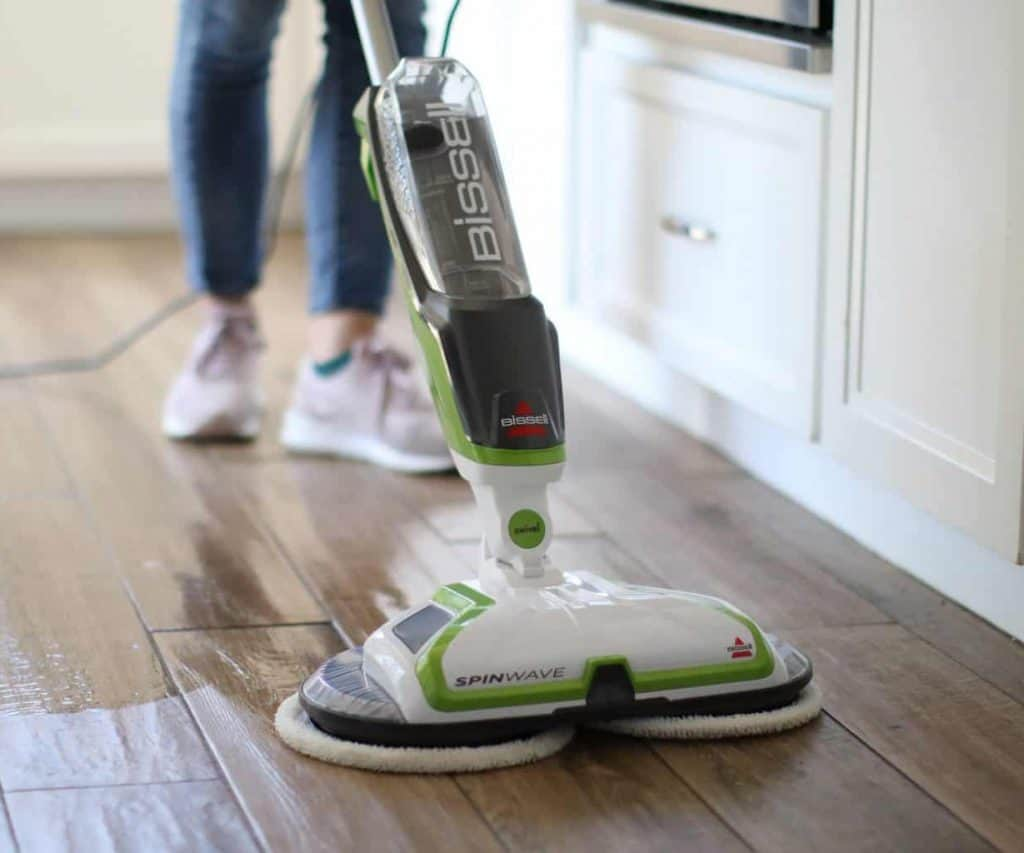 Woman cleaning wood floors with dog pee mop