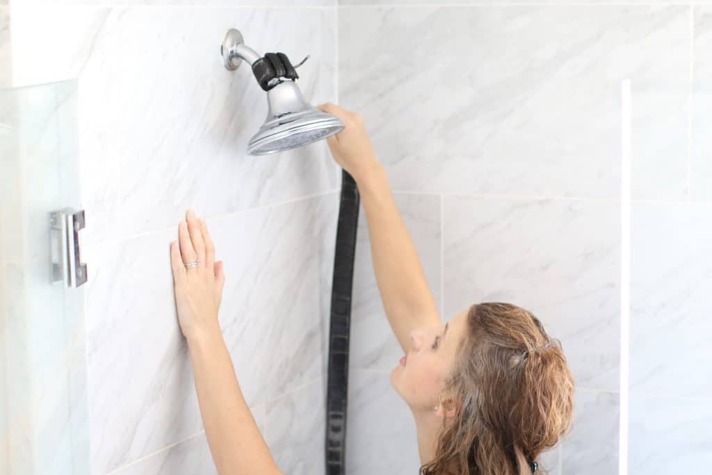 Woman trying to remove her shower head without a wrench
