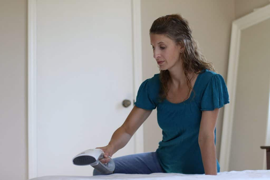 Woman sitting down her bed while holding a steam cleaner