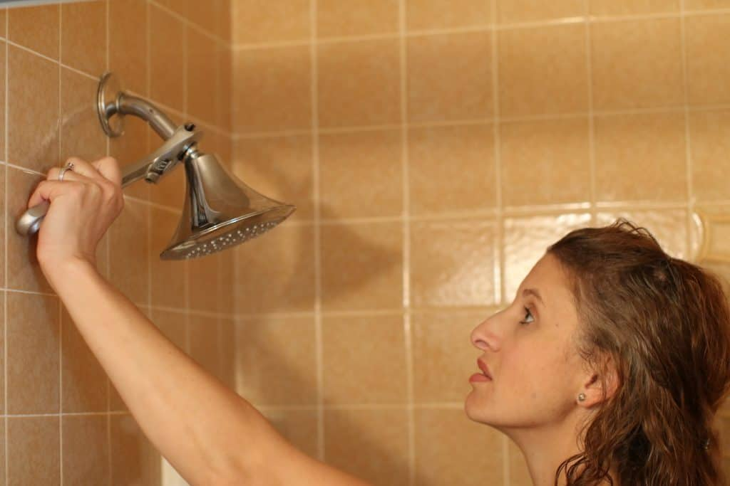 Woman using a wrench to stop her shower head from dripping