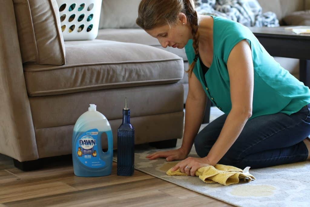 Woman cleaning her area rug on a hardwood floor