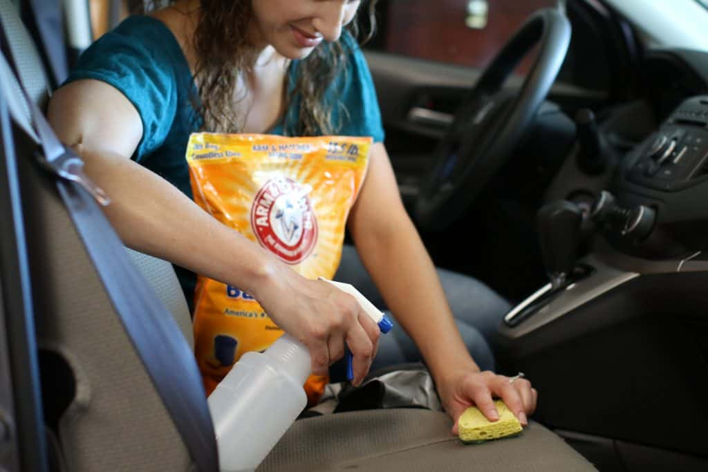 Woman using a baking soda cleaning solution to clean her car seats