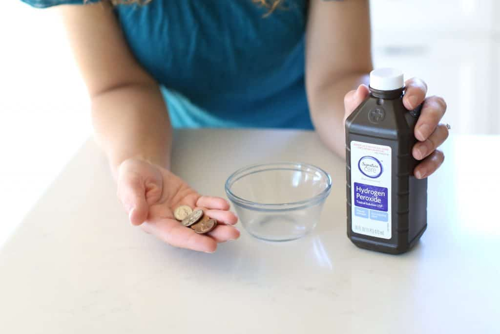 Woman holding coins and hydrogen peroxide