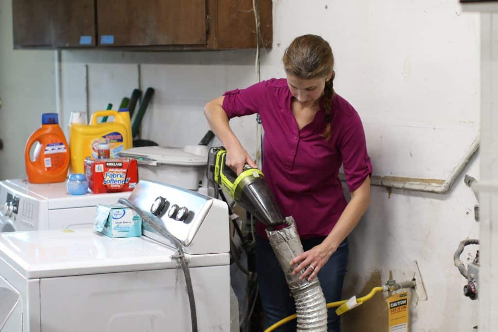 Woman using a vacuum to clean dryer vent