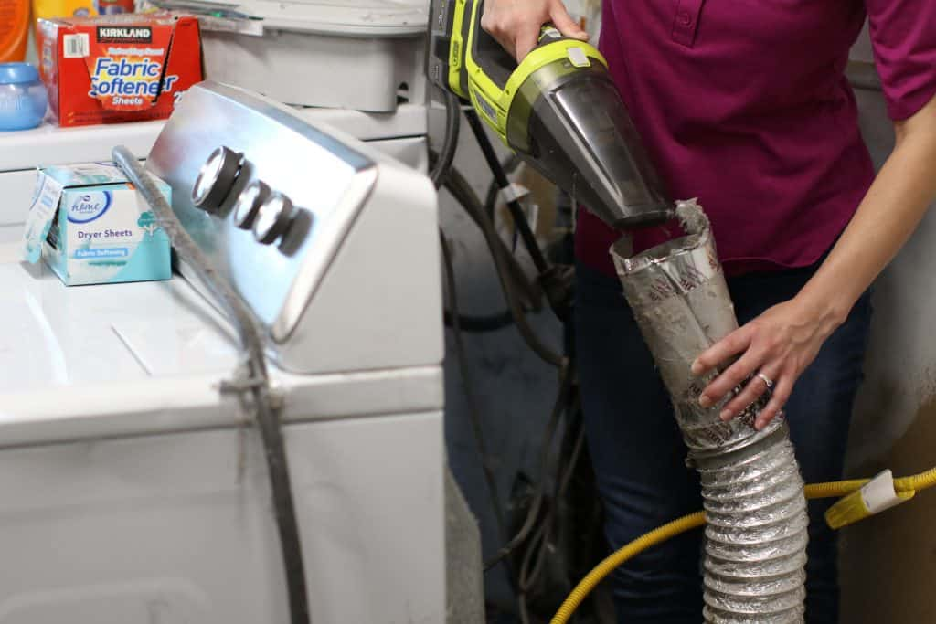Close up of a person using a vacuum to clean dryer vent