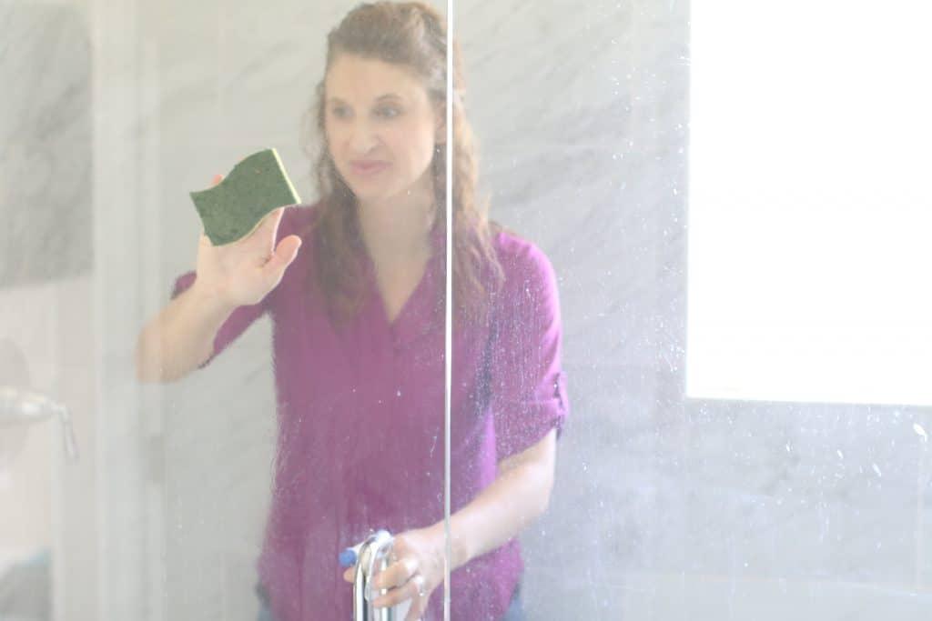 Woman scrubbing a tempered glass shower door