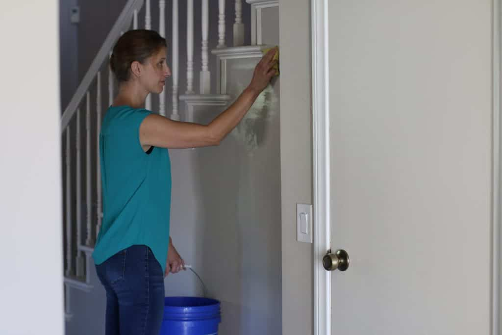 Woman cleaning her walls that has flat paint