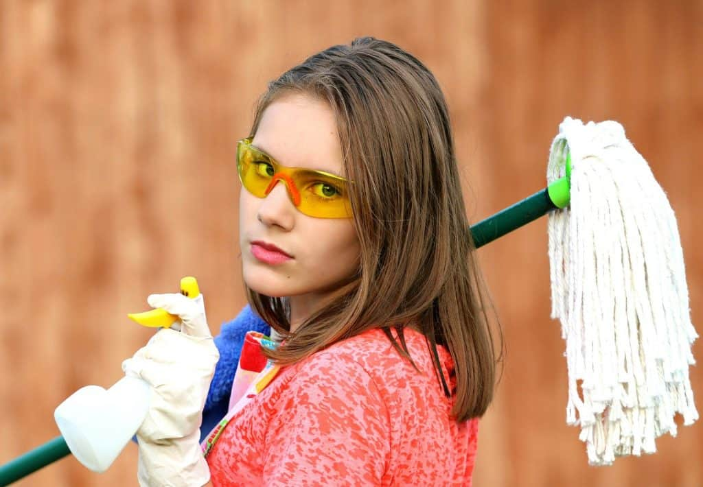 Woman holding a spray and mop