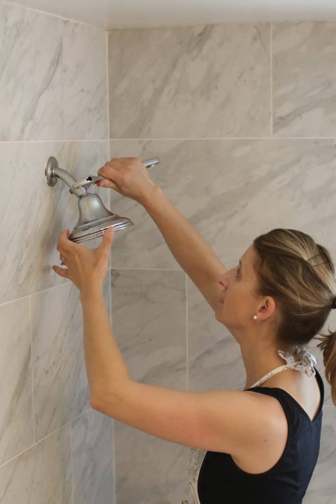 Woman removing a shower head