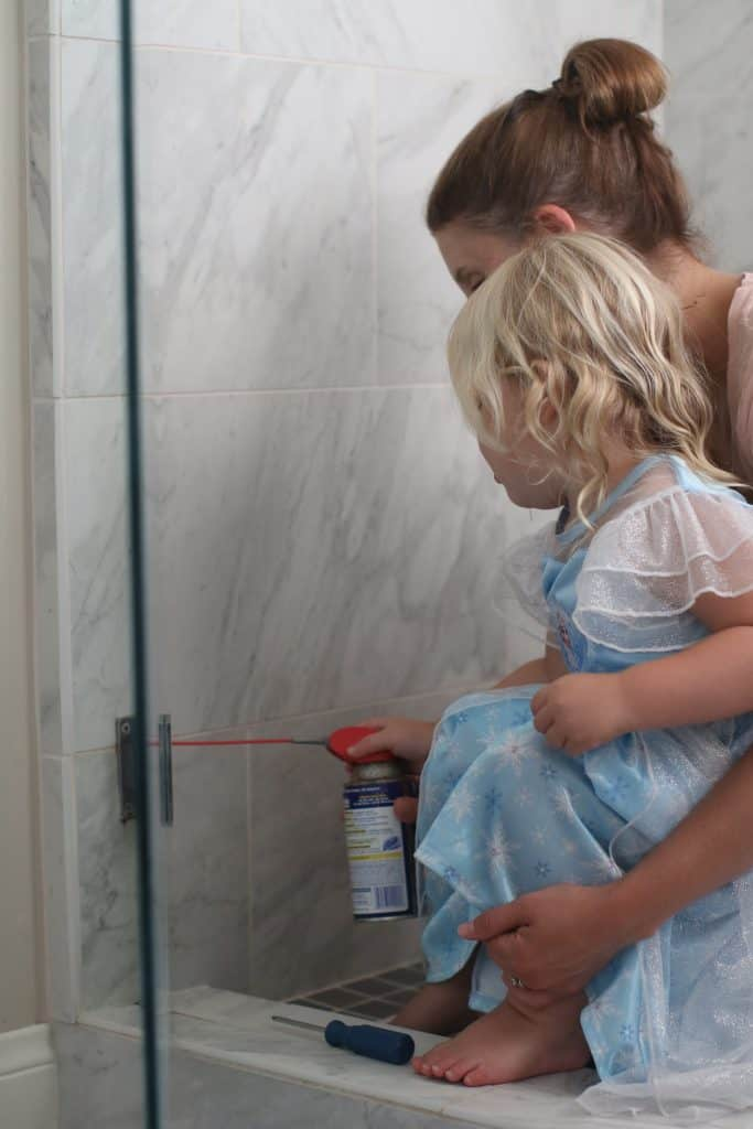 Mother teaching her daughter how to fix their shower doors