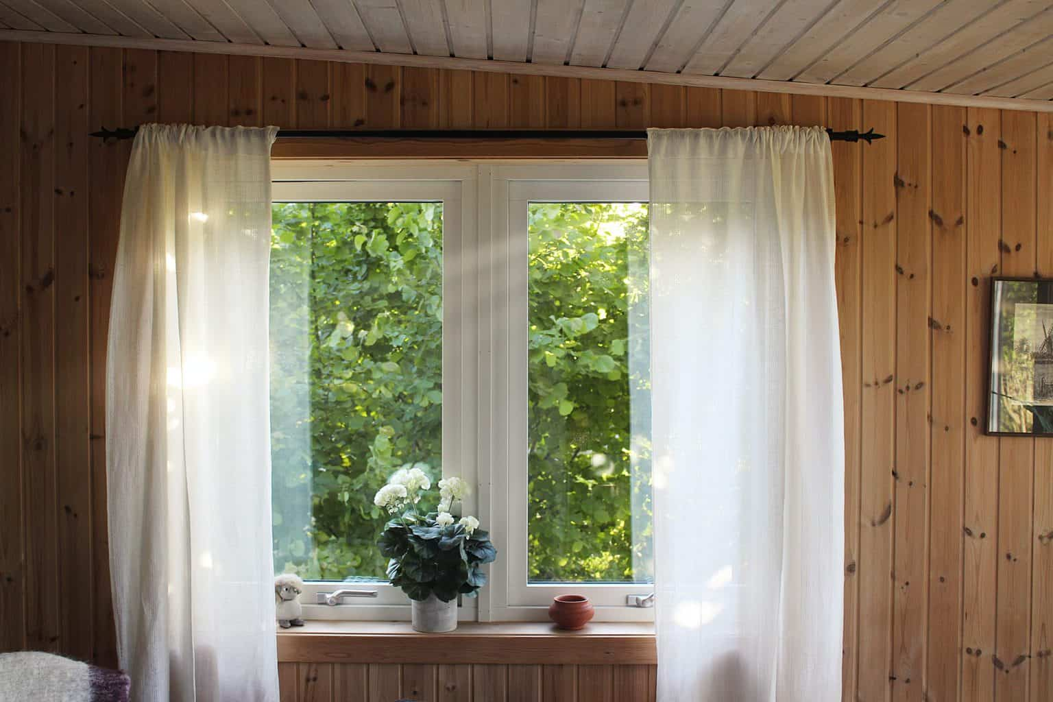 White curtains covering a white aluminum window frame