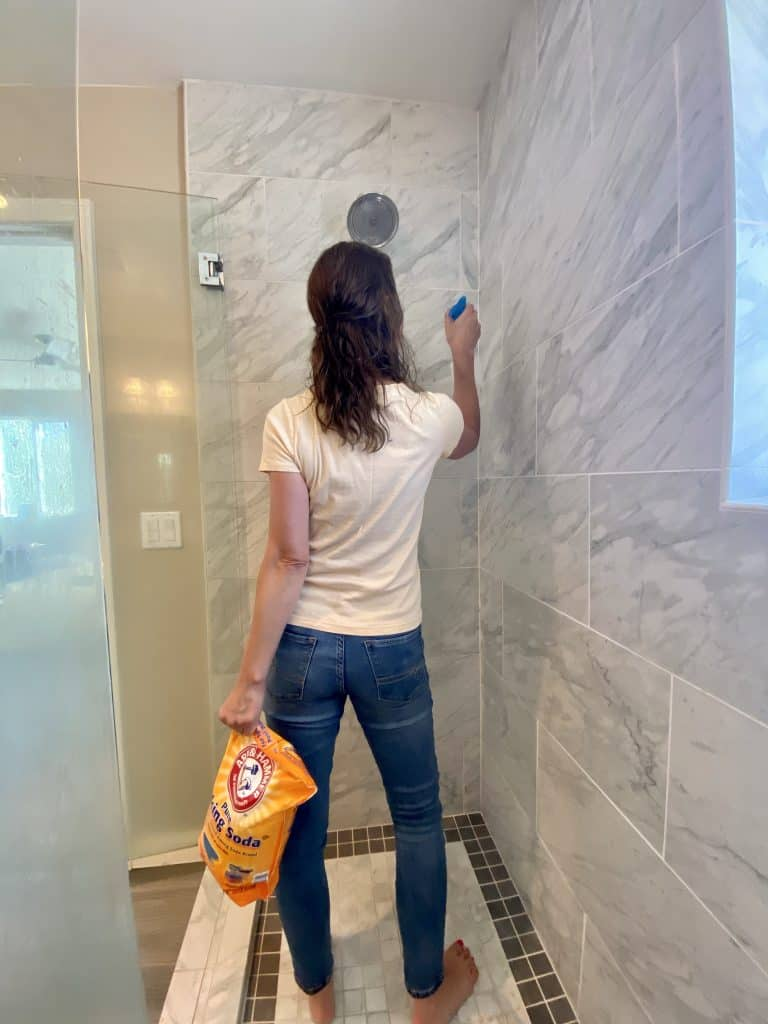 Woman holding a bag of baking soda while cleaning her shower