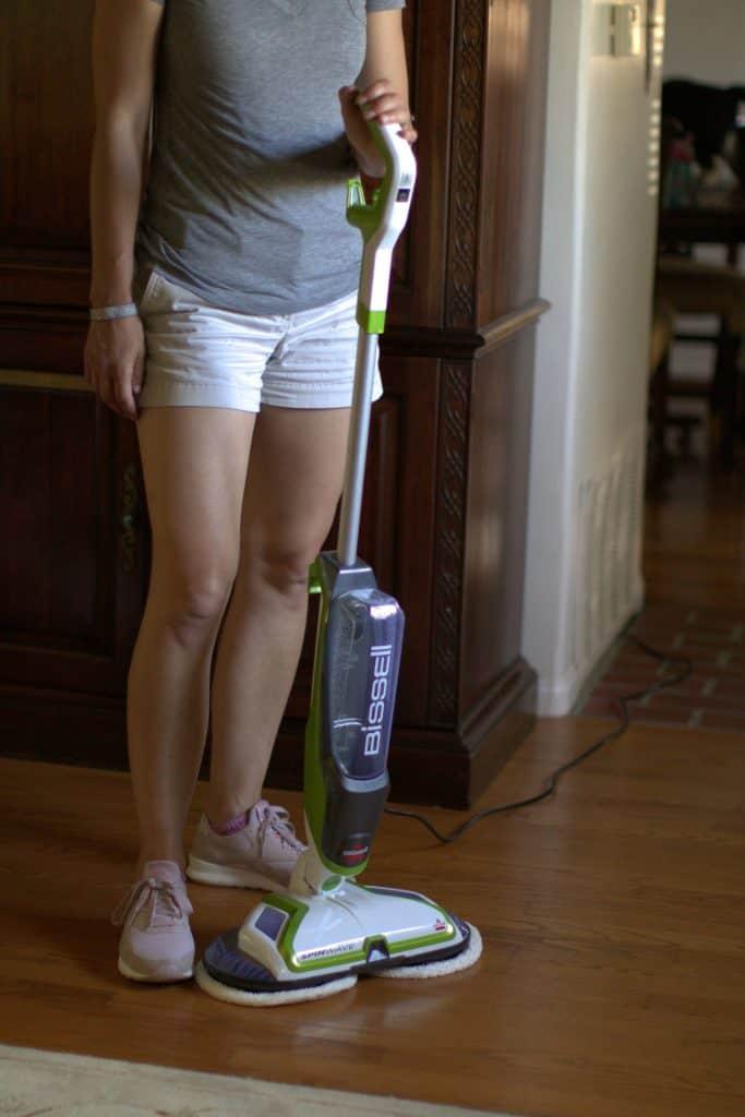 Woman standing beside a mop