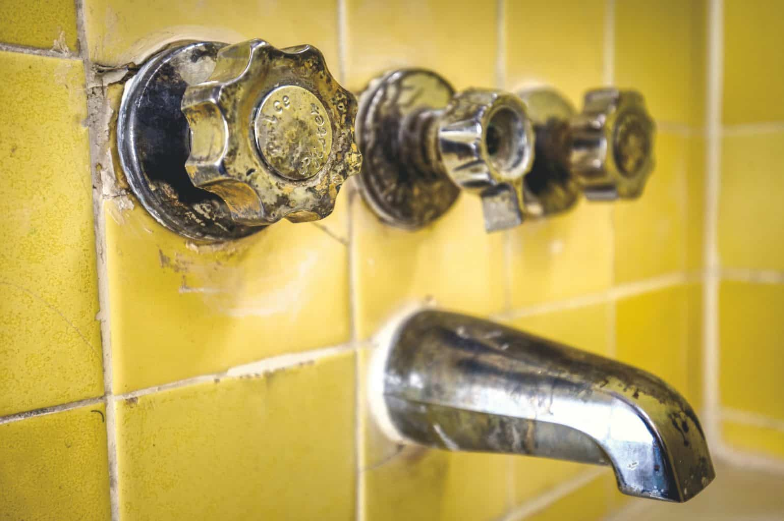 A messy and broken bathroom yellow wall tiles