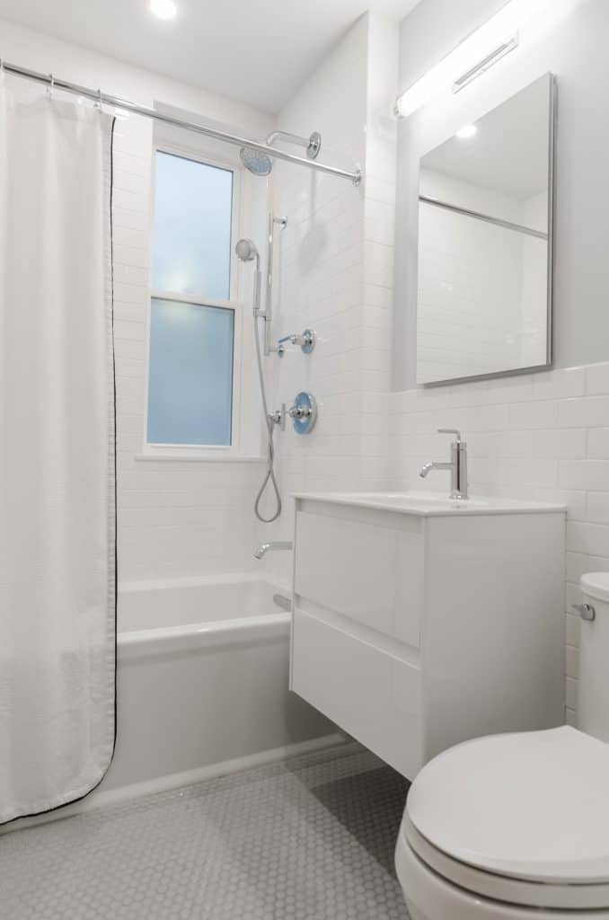 A white toned cultured marble shower with a window and a mirror
