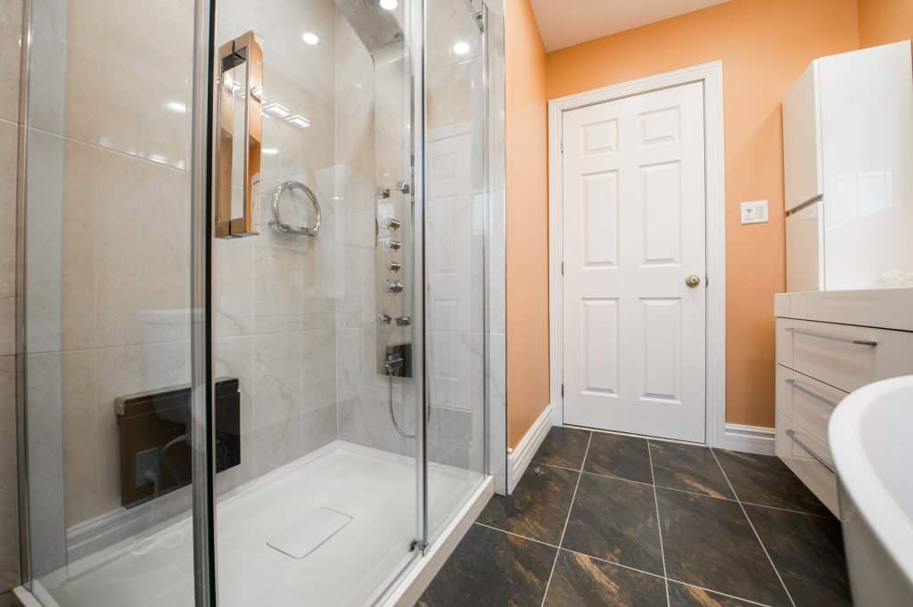 A bathroom with a plastic shower floor in the shower