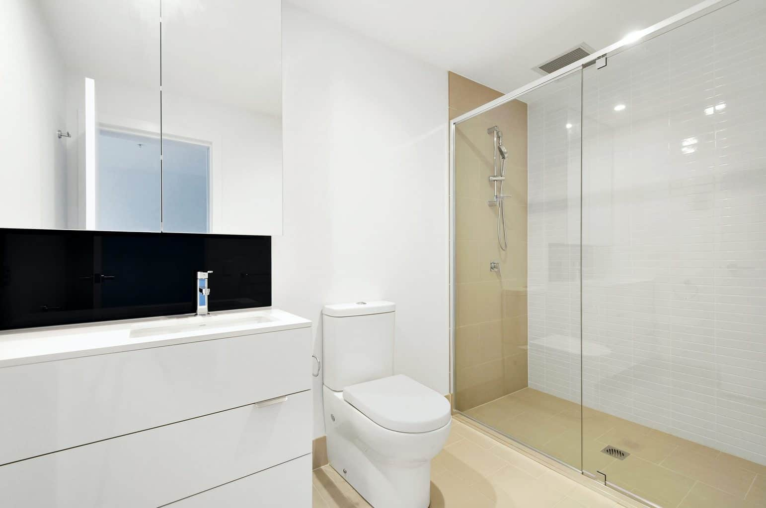 A bathroom with a glass shower door