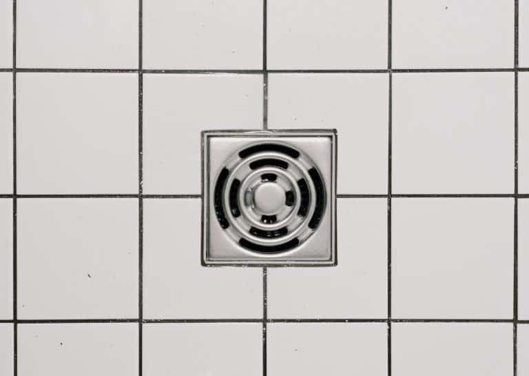 A shower drain with white tiles