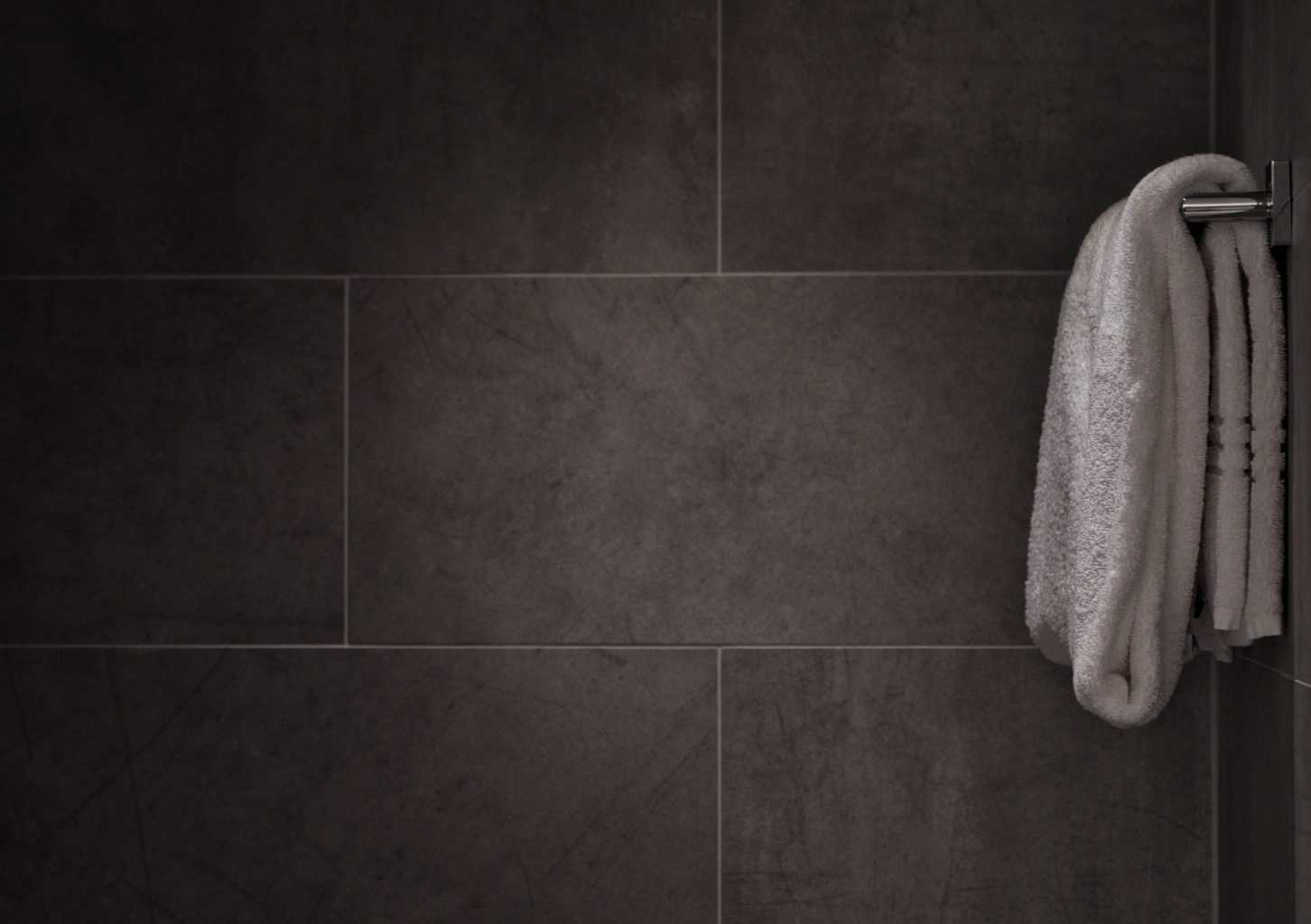 Black toned wall slate tiles with a towel hanged