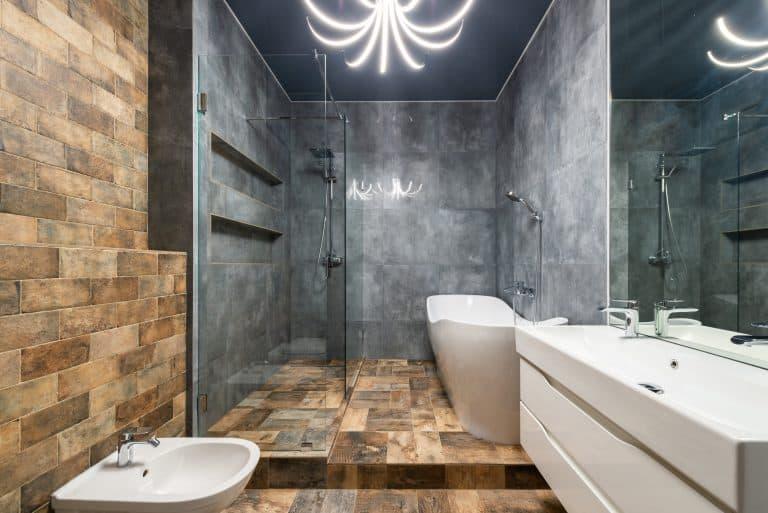 A bathroom with a stone shower floor and a bathtub