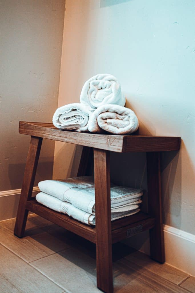 A teak shower bench with white towels