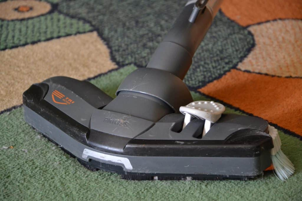 A carpet cleaner with messy brushes on a carpet