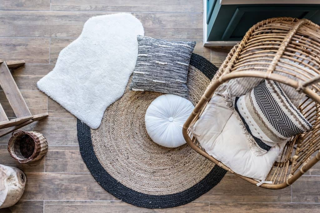 a cowhide rug on the floor with another rug, a variety of pillows and a swing chair