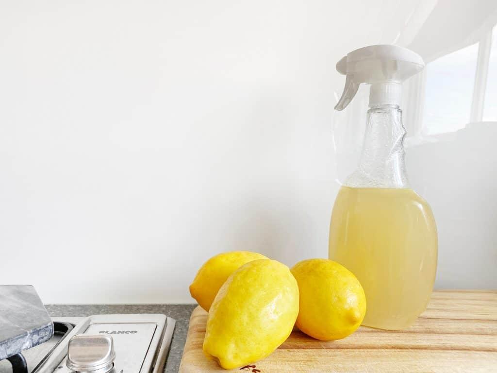 three lemons and a bottle of spray almost full of lemon juice
