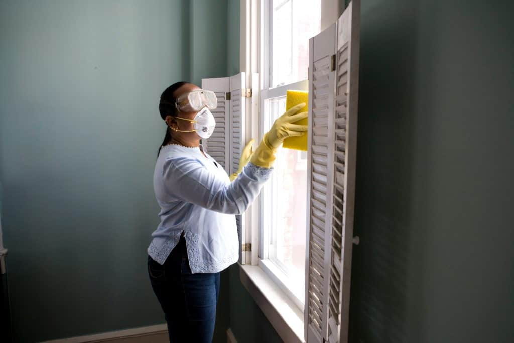a woman wearing mask cleaning a window