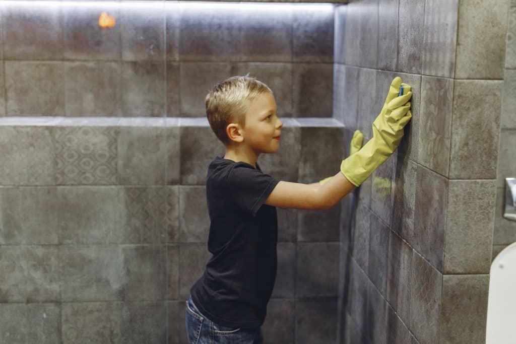 a kid scrubbing a brick wall with sponge