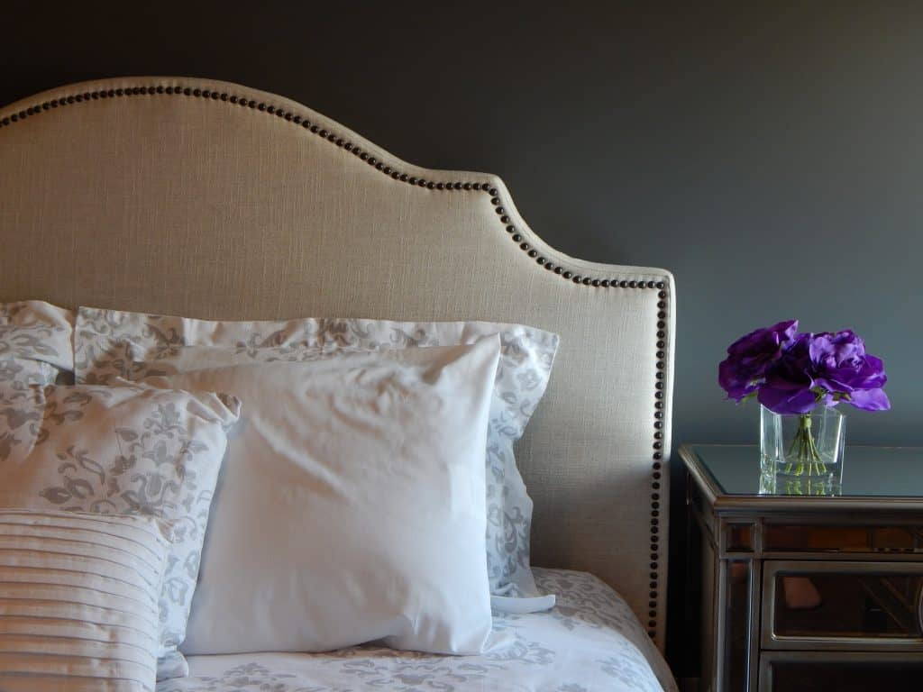 A white bed headboard with white pillows