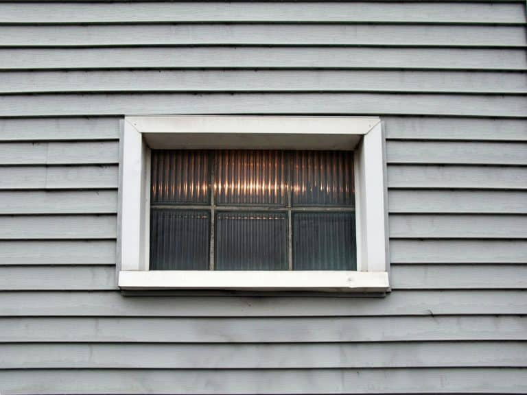 A block window outside with vinyl siding